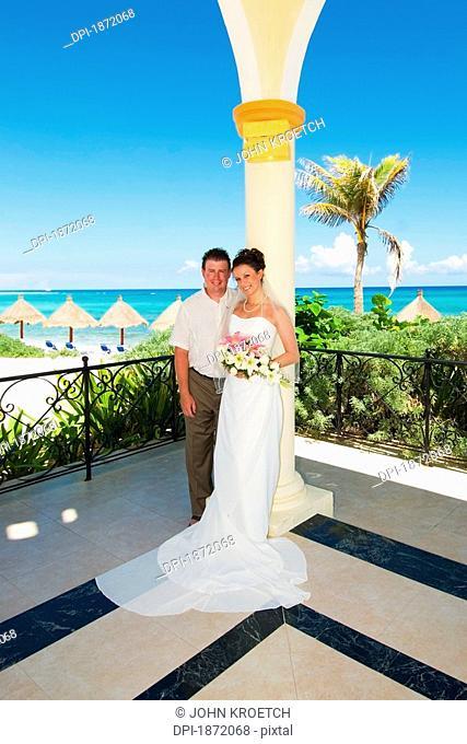 akumal, riviera maya, mexico, a bride and groom in a gazebo by the beach at gran bahia principe tulum all-inclusive resort