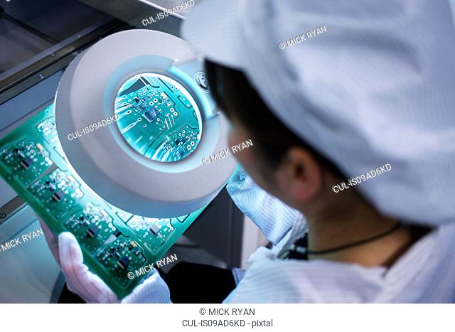 Worker at small parts manufacturing factory in China looking through magnifier at microchips