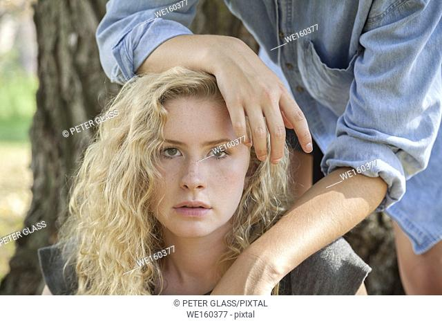 Blonde teenage girl outdoors, with hands from another teenage girl resting on her