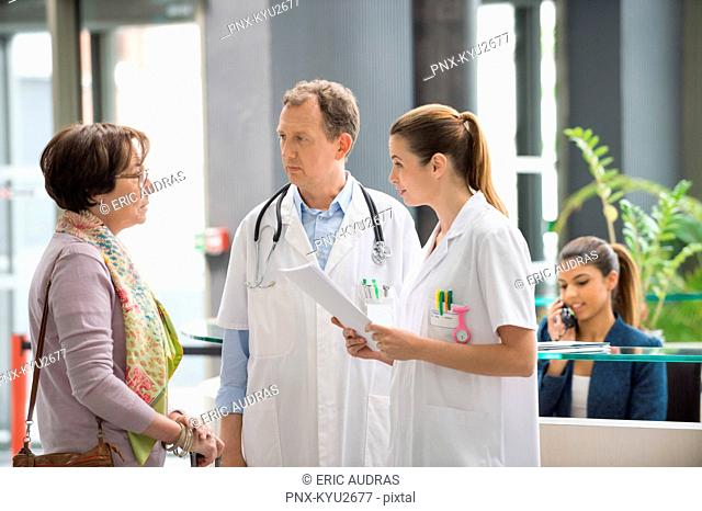 Doctors discussing with female patient at hospital reception desk