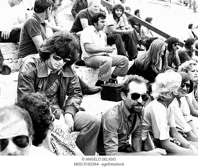 Claudio Baglioni (Claudio Enrico Paolo Baglioni), the Italian singer-songwriter, sitting on the bleachers of an amphitheater. Italy, 1975