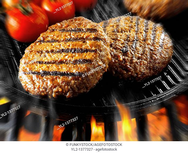 Beef burgers being cooked in a skillet with flames