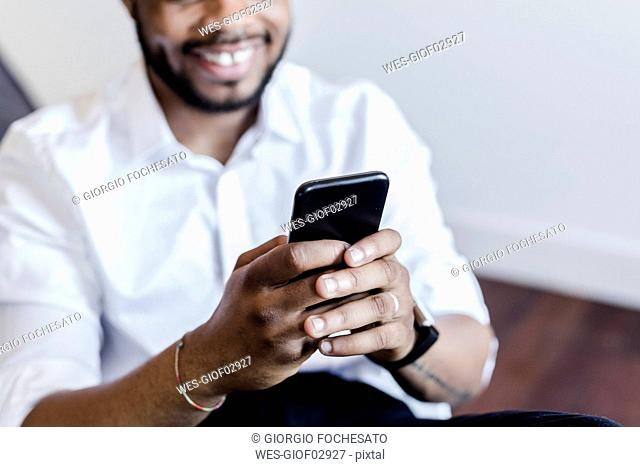 Close-up of smiling man using cell phone