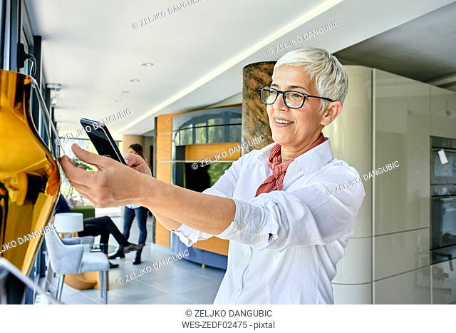 Mature woman scanning price tag with a smartphone in a showroom