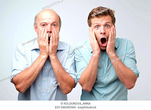 Frightened two men have scared expressions, look nervously, isolated over white background. Emotive mature father and son have shocked faces