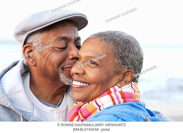 African American man kissing wife