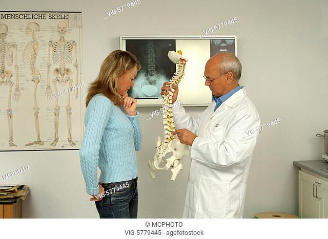 Arzt zeigt der Patientin anhand einer Wirbelsaeule die Schmerzursache, Hamburg 2005 - Germany, 09/11/2005