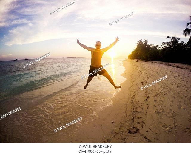 Portrait of exuberant man jumping on tropical beach at sunset