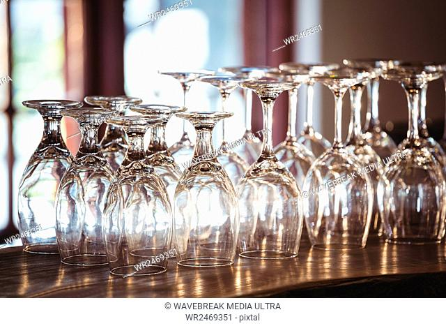 Empty wine glasses arranged on bar counter at bar