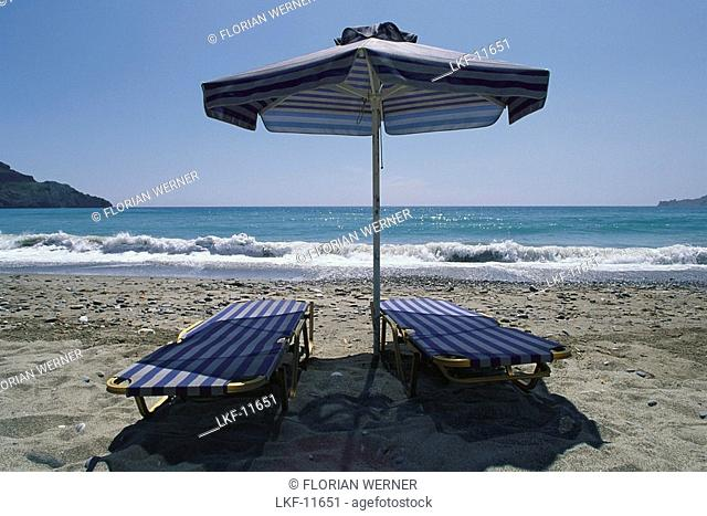 Two sun loungers and a sunshade on Plakias beach, Crete, Greece