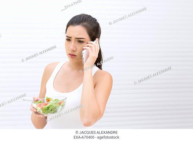 woman eating salad, phone call