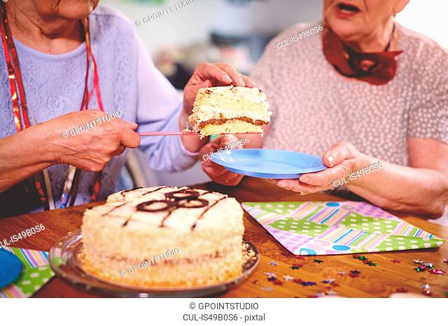 Senior women serving birthday cake at party