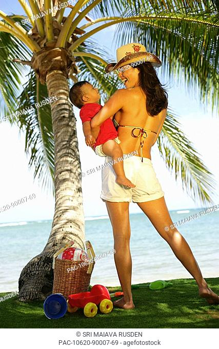 Beautiful local mother holding little boy next to ocean and palm tree, beach toys in grass at her feet