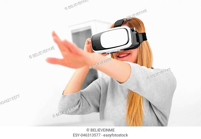 Virtual reality goggles. An attractive young woman uses virtual reality glasses in a bright room. Focus on the glasses