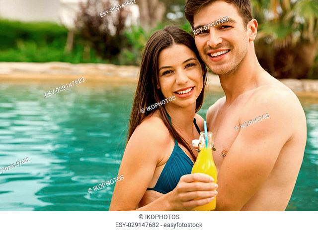 Young couple inside the pool and drinking natural juices