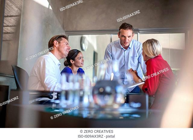 Male designer presenting to team meeting at conference table in design office