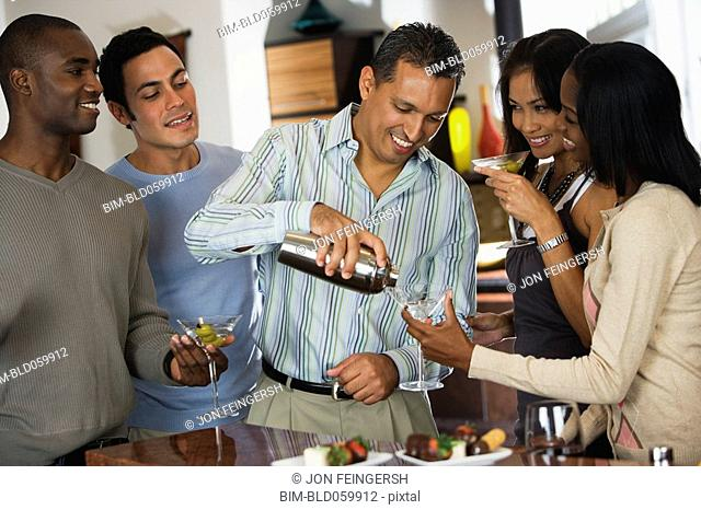 Hispanic man pouring drink at party