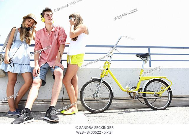 Three teenage friends with headphones and bicycle
