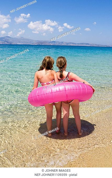 Two girls in one inflatable ring standing on beach and looking at sea