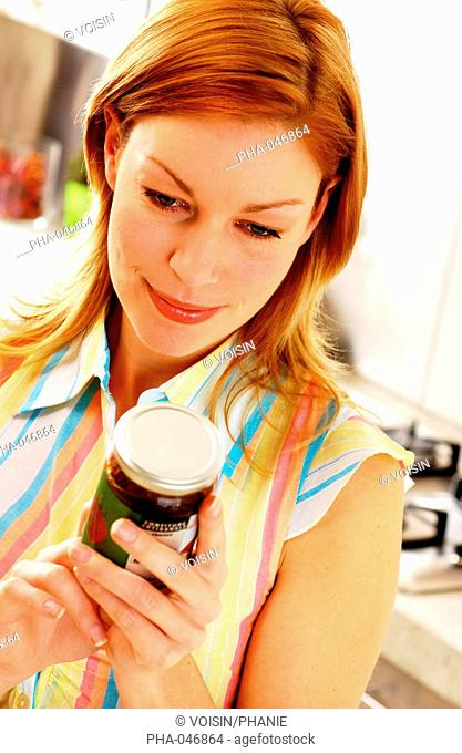 Woman checking the expiration date on a jar of jam