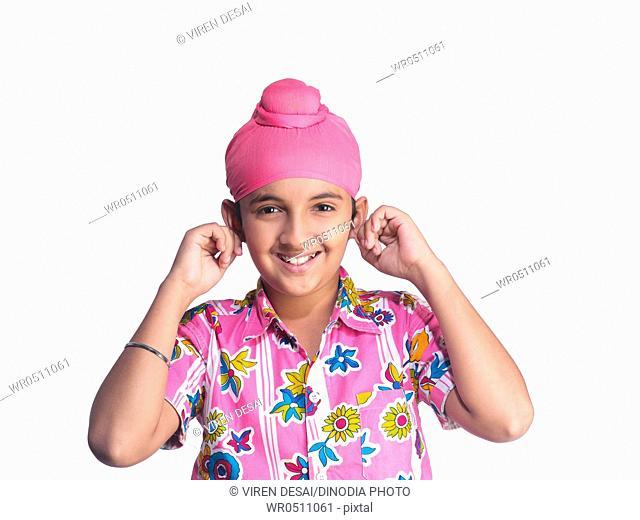 Portrait of Sikh boy holding both ears MR702Y
