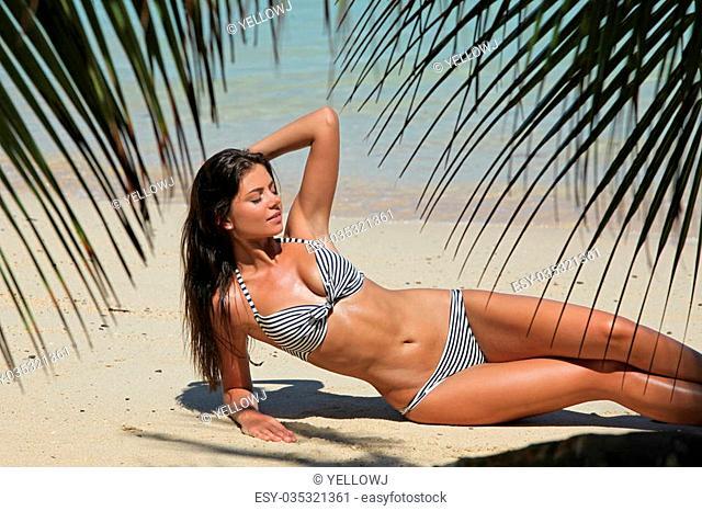 Woman in bikini laying on tropical beach