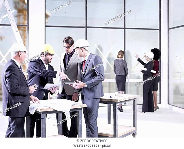 Businessmen talking in office under construction