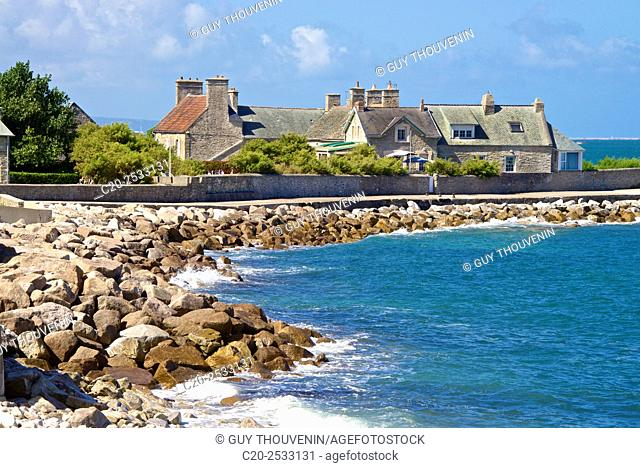 Lovely cove with Rocky beach and blue sea with typical breton house in the background, Digosville near Cherbourg harbor, Pointe de la Porte