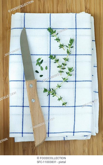 Thyme sprigs and leaves on a tea towel with a knife