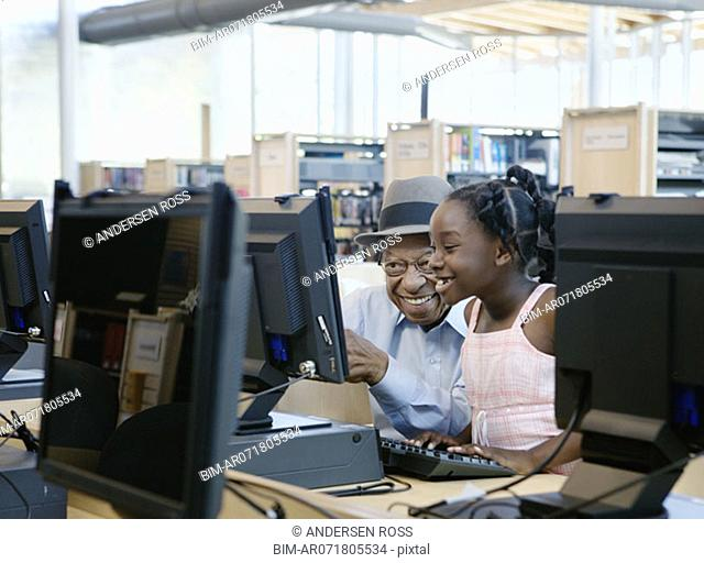 Man and girl using library computers