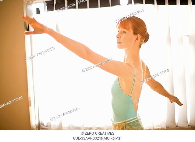 Ballet dancer posing in front of window