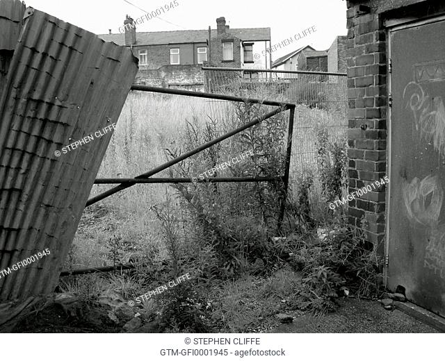 View of a dilapidated housing area and overgrown garden