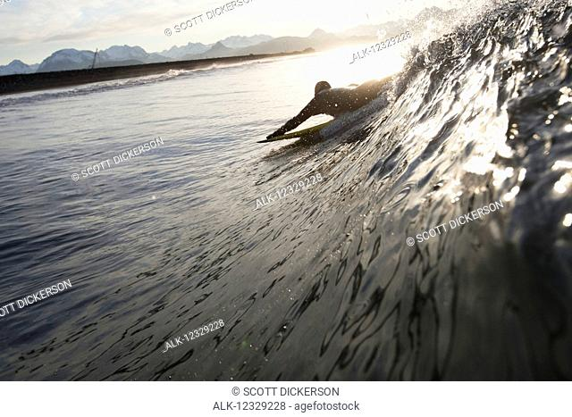 Silhouette of a surfer picking up a wave, Southeast Alaska; Yakutat, Alaska, United States of America