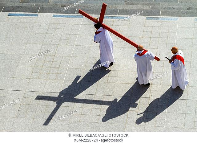 Priest with a cross in Holy Week. Rosary Basilica square. Lourdes city