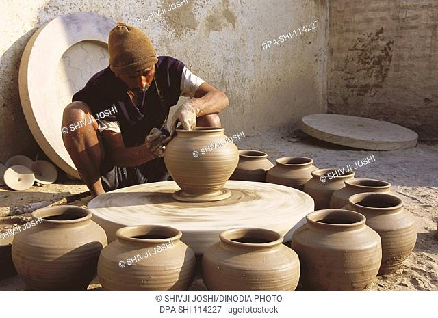 Pottery ; potter giving shape to clay pot on wheel ; Bikaner ; Rajasthan ; India