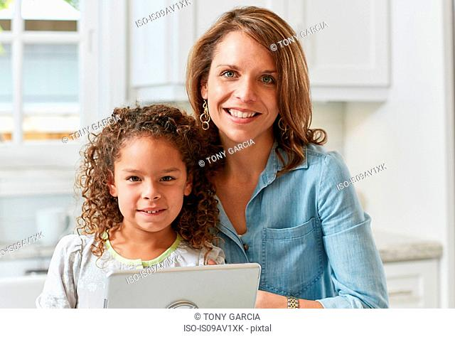 Mother and daughter in kitchen with digital tablet looking at camera smiling