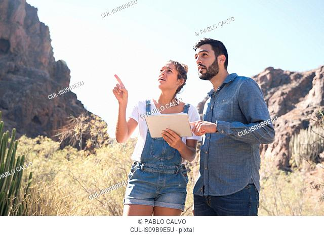 Young hiking couple looking up and pointing from valley, Las Palmas, Canary Islands, Spain