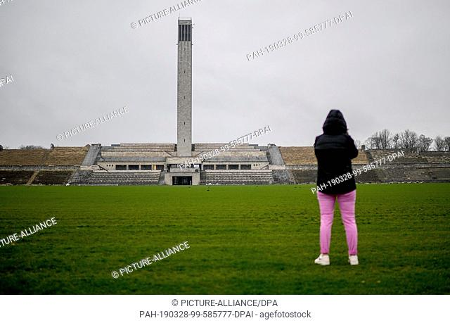 28 March 2019, Berlin: A young woman photographs the bell tower on the edge of an event on the future and perspective of the Olympic Park