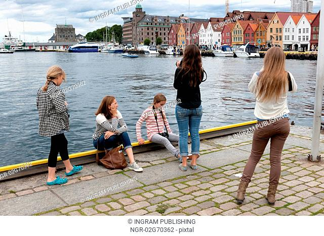Girls taking picture of a city, Bryggen, Bergen, Norway