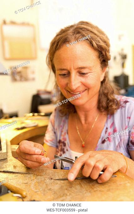 Germany, Bavaria, Munich, Mature woman working on ring in her workroom at home
