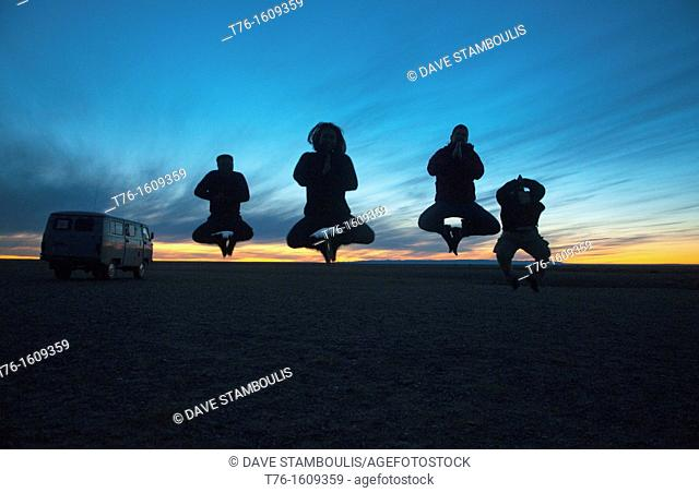 jumping tourists sillhouetted at sunset in the Gobi Desert of Mongolia