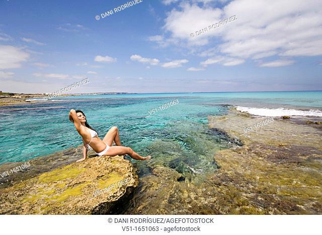 Young woman in bikini sitting on the rocks and enjoying the sea in Formentera, Spain