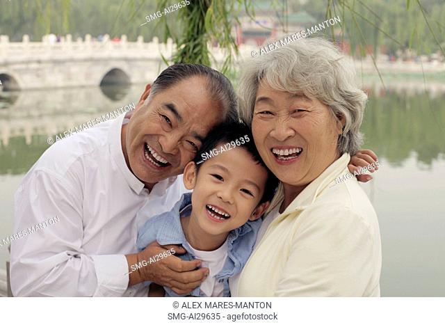 Grandma, grandfather and grandson hugging in a park