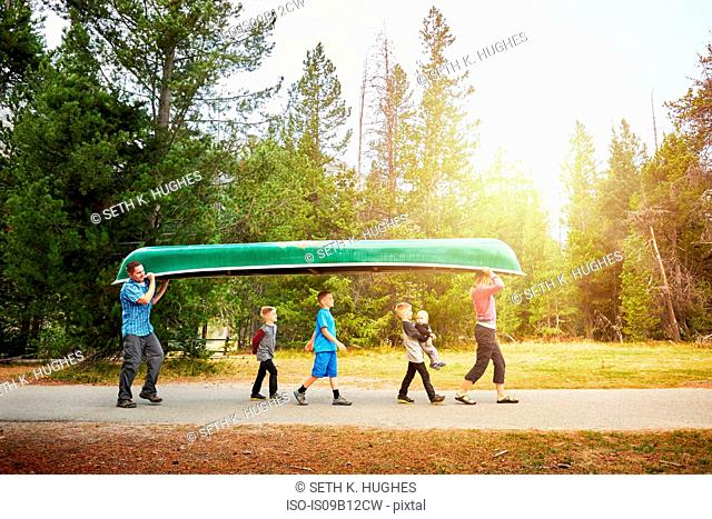 Family with four children carrying canoe, Grand Teton National Park, Wyoming, USA