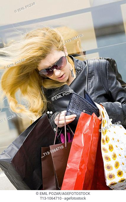 Shopping rush, pretty young woman is looking into her wallet and the wind is blowing her long blonde hair