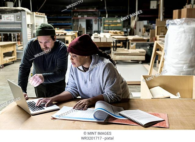 A Caucasian male carpenter and a Black female carpenter working on a laptop computer after work hours in a large woodworking factory