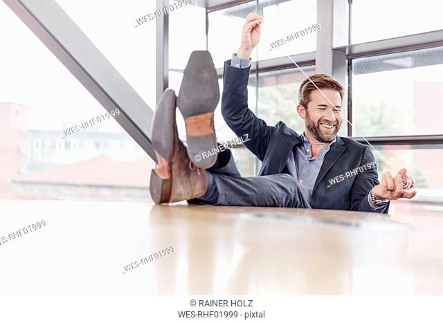 Happy businessman putting his feet on the table playing with yoyo