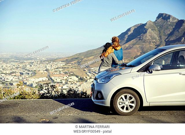 South Africa, Cape Town, Signal Hill, two young women leaning against car overlooking the city