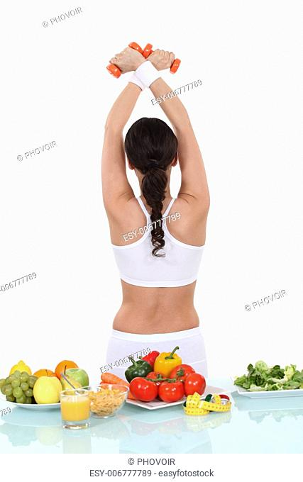 healthy food on table and sporty woman back turned