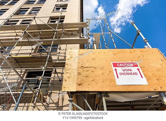 "Sign reading, """"Caution, Work Overhead"""" in a construction area"